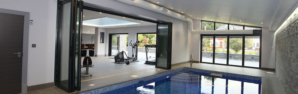 Bi-fold doors opening up to an indoor swimming pool, installed by Paradise Windows in Oxford