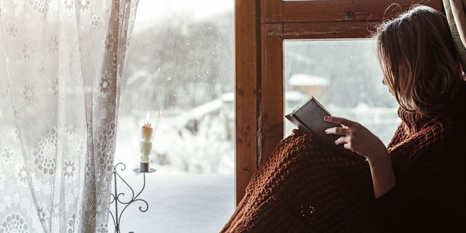 Lady Sat Next to Timber Windows Reading a Book, wearing a Blanket